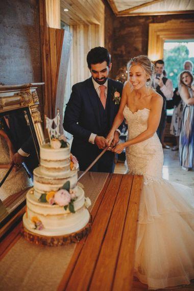 Bride and Groom Cut Wedding Cake At Rustic Wedding