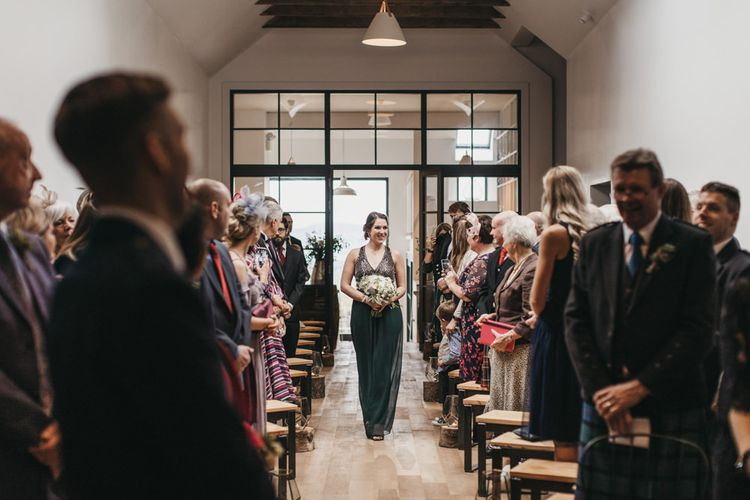 Bridesmaid walks up aisle during ceremony at Guardswell Farm