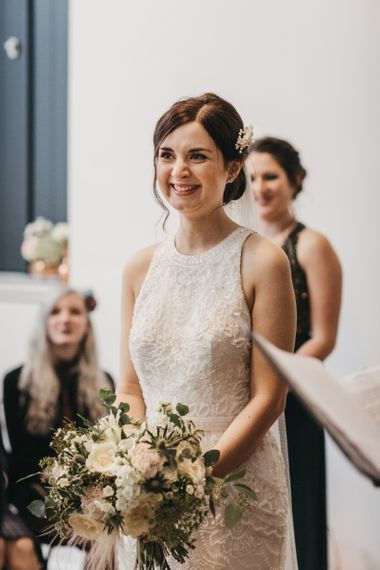 Bride with updo and hair accessory clutching white wedding bouquet