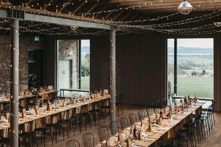 Rustic wedding breakfast at Guardswell Farm with fairy light canopy