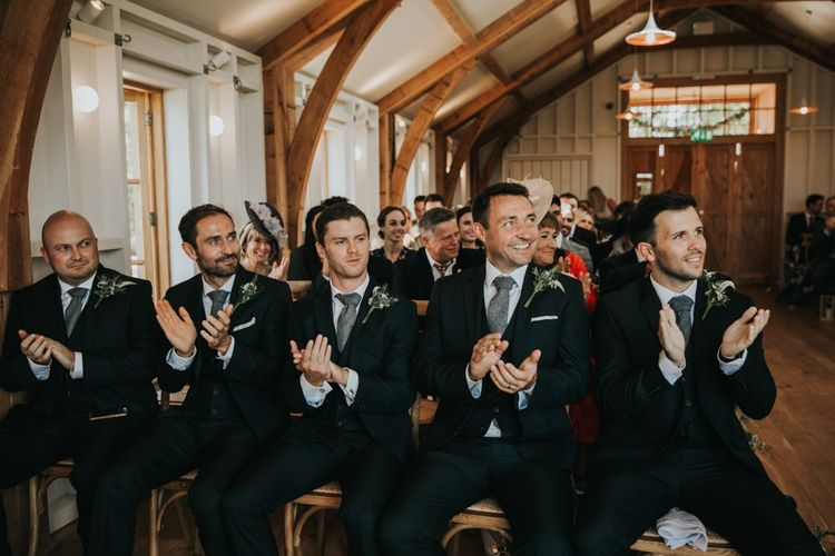 Groomsmen applaud the couple during ceremony