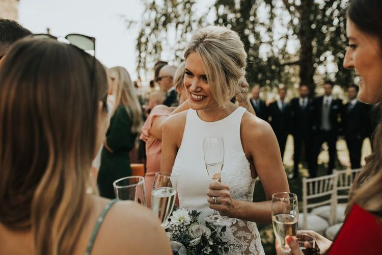 Bride sips champagne whilst mingling with guests during Hyde House wedding