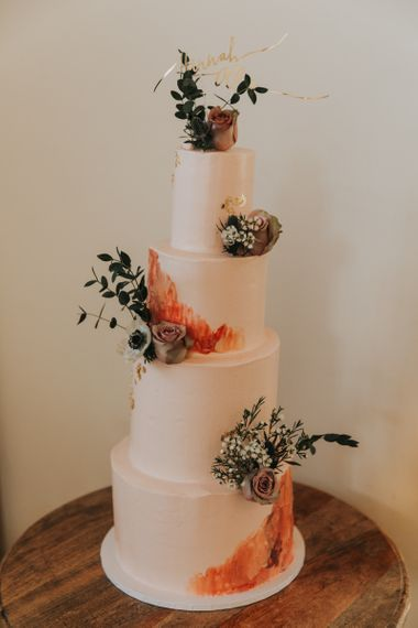 Pink wedding cake with flower and foliage decor