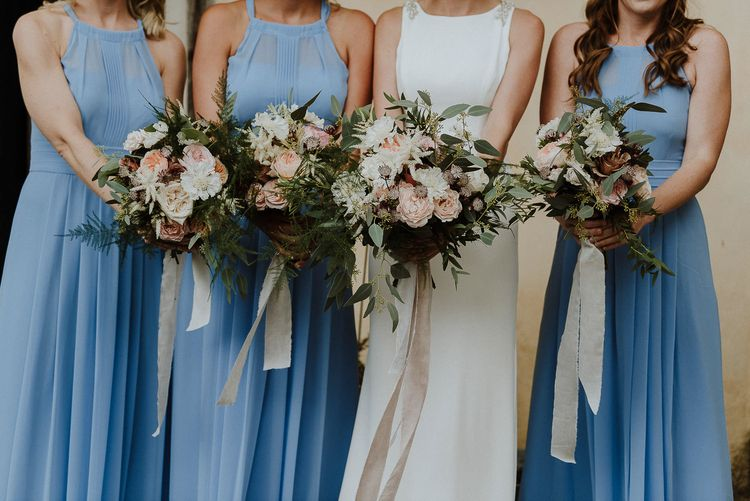 Bride and Bridesmaids in Blue Halterneck Dresses Holding Their Bouquets