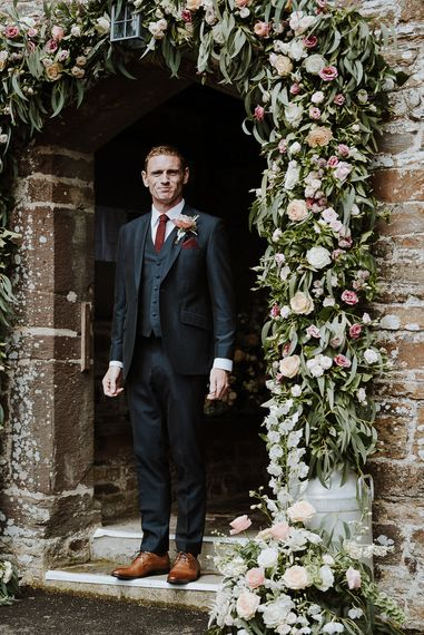 Groom in Three-piece Clifton Suit Standing Next to a Church Floral Arch