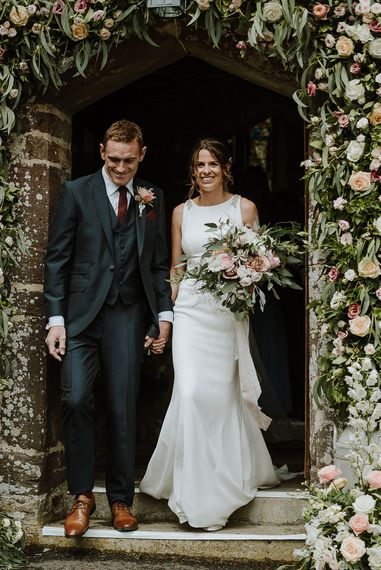 Bride in Mikaella Bridal Wedding Dress and Groom in Three-piece Clifton Suit Exiting The Church Under a Floral Arch