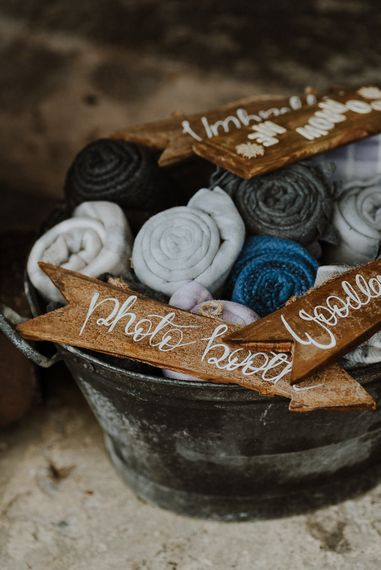 Metal Basket Filled with Rolled Blankets and Wooden Arrow Wedding Signs