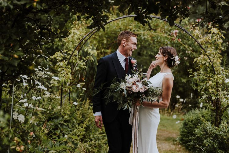 Bride in High Neck Mikaella Bridal Fitted Wedding Dress and Groom in  Clifton Suit Laughing