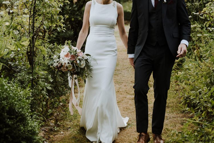 Bride in High Neck Mikaella Bridal Fitted Wedding Dress and Groom in  Clifton Suit Holding Hands