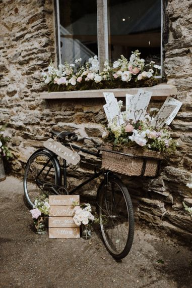 Vintage Bicycle Basket Filled with Flowers as a Wedding Table Plan with Wooden Signs