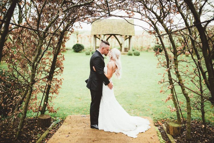 Bride  in Danni Made With Love Bridal  Wedding Dress and Groom in Reiss Suit Kissing