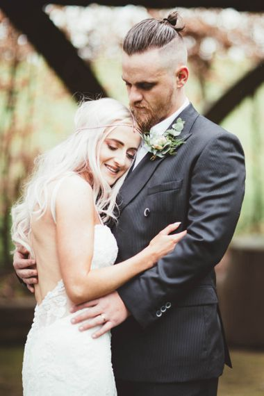 Bride  in Danni Made With Love Bridal  Wedding Dress and Groom in Reiss Suit Embracing