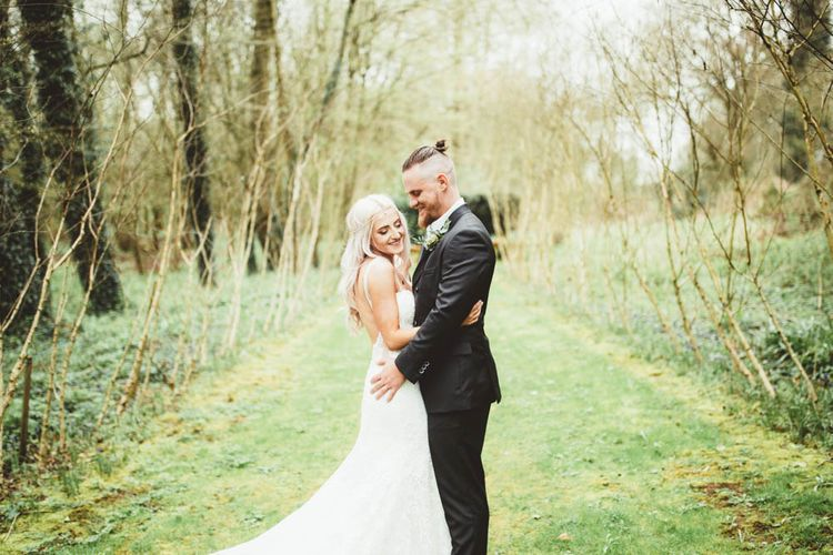 Bride in Danni Made With Love Bridal Wedding Dress and Groom in Reiss Suit Cuddling in the Countryside