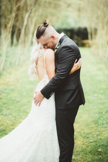 Bride in Danni Made With Love Bridal Wedding Dress and Groom in Reiss Suit Embracing in the Countryside