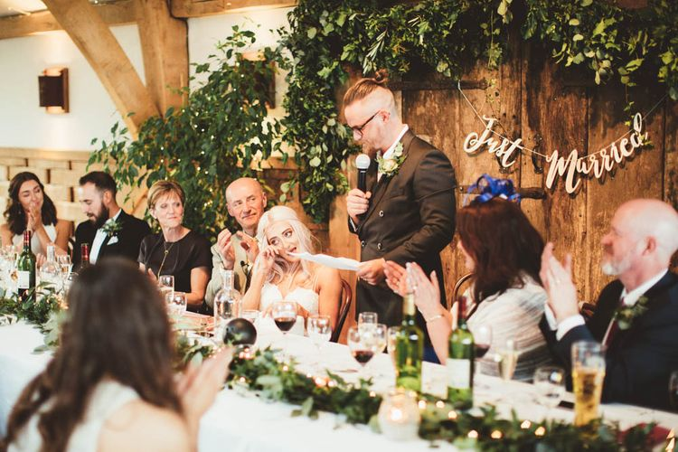Groom in Reiss Suit  Giving His Wedding Speech with Greenery Back Drop and Copper Just Married Bunting