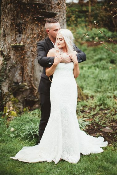 Bride in Danni Made With Love Bridal Wedding Dress and Groom in Reiss Suit Embracing in the Woodland