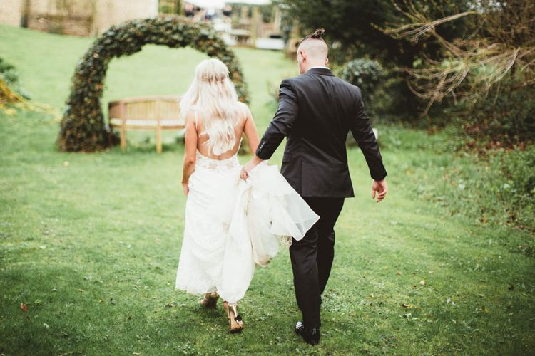Bride in Danni Made With Love Bridal Wedding Dress and Groom in Reiss Suit Walking Through the Gardens