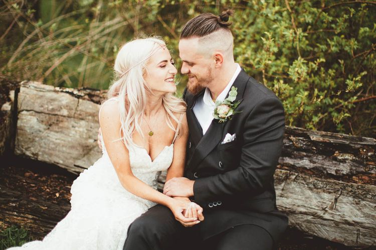 Bride in Danni Made With Love Bridal Wedding Dress and Groom in Reiss Suit Cuddling on a Log