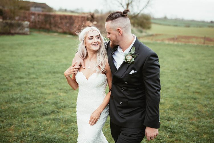 Bride in Danni Made With Love Bridal Wedding Dress and Groom in Reiss Suit Arm in Arm in the Field