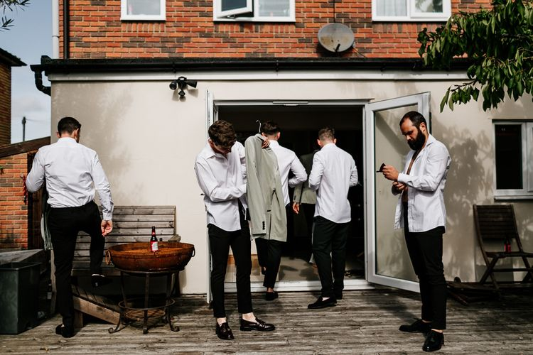 Groomsmen Getting Ready in Black Trousers and Grey Tuxedo Jackets