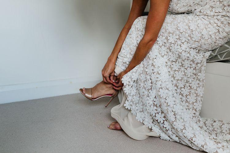 Bride putting on her Gold Oscar Tiye – Satin Champagne Minnie Shoes