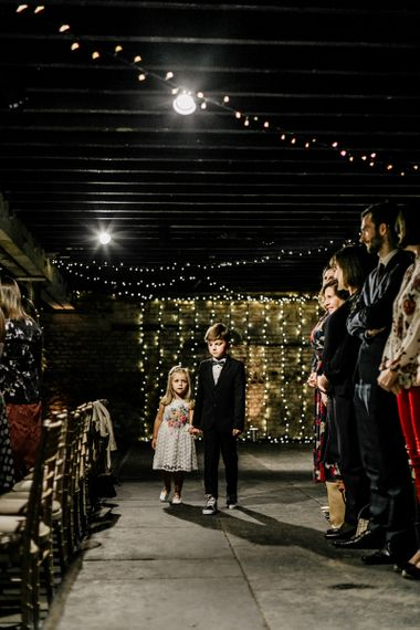 Page Boy and Flower Girl Walking down the Aisle with Fairy Light Wedding Decor