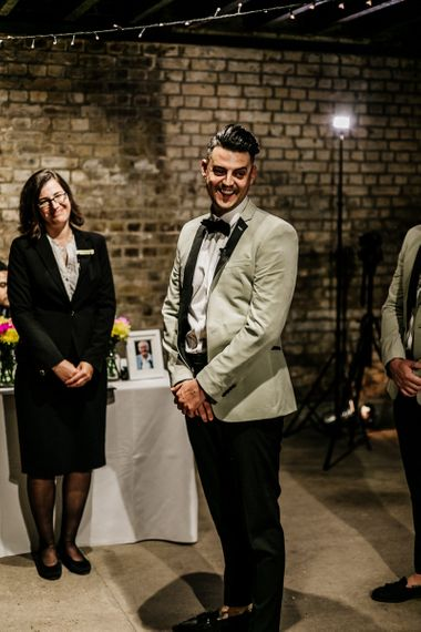 Stylish Groom in Black Trousers and Grey Tuxedo Jacket Waiting at the Altar