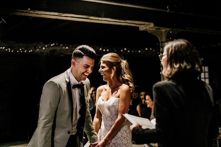 Bride in Lace Tara Keely Wedding Dress and Groom in Grey Tuxedo Jacket Laughing at the Altar