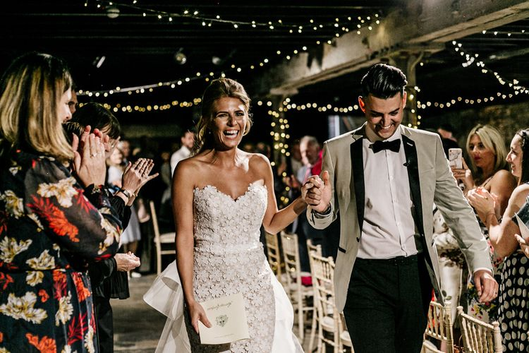 Bride in Tara Keely Wedding Dress and Groom in Grey Tuxedo Jacket Walking Up the Aisle After Saying I Do