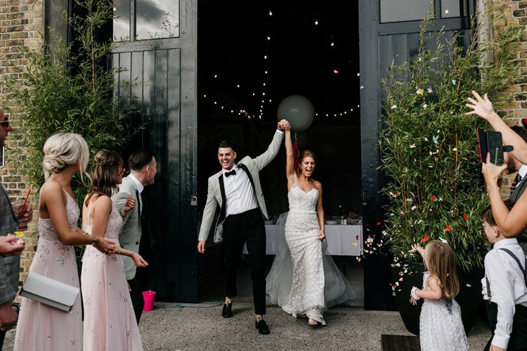 Bride in Tara Keely Wedding Dress and Groom in Grey Tuxedo Jacket Exiting Wedding Venue Hand in Hand