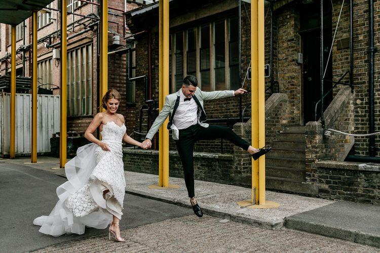 Bride in Tara Keely Applique Wedding Dress and Groom in Grey Tuxedo Jacket Jumping for Joy