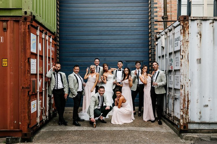Wedding Party Portrait with Stylish Groomsmen in Black Trousers with Grey Tuxedo Waistcoats, Bridesmaids in Pink Strappy Dresses and Bride in Lace Tara Keely Wedding Dress