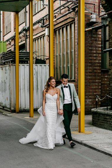 Bride in Off the Shoulder Tara Keely Wedding Dress with Detachable Organza Skirt and Groom in Grey Tuxedo Jacket