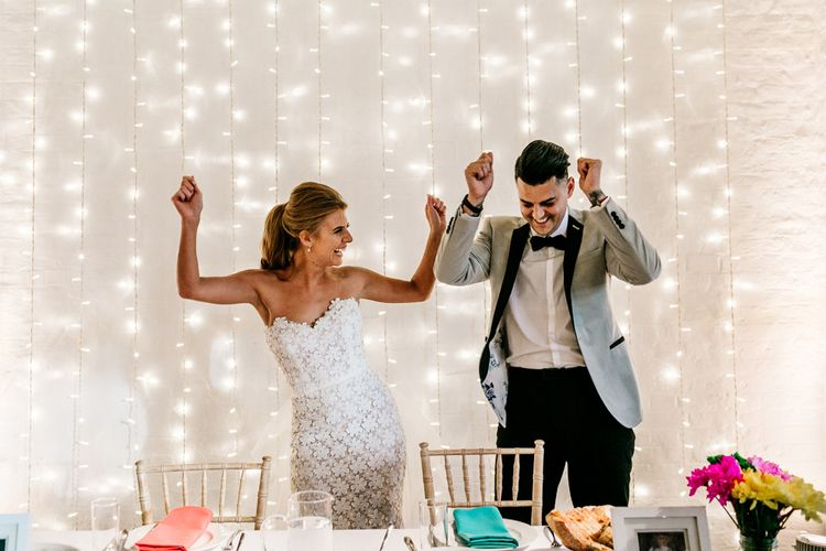 Bride and Groom Standing In Front of a Fairy Light Backdrop