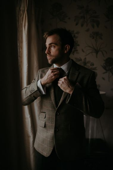 Groom in brown check suit on the wedding morning