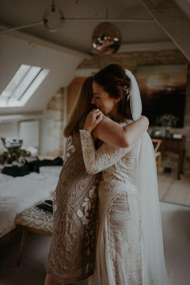 Bride and bridesmaid hugging on wedding morning
