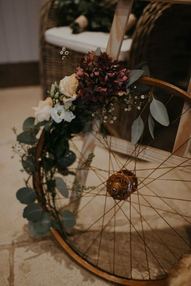 Vintage wheel wedding decor covered in flowers