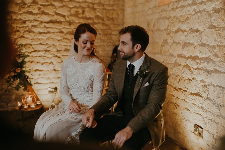 Bride in lace wedding dress and groom in wool suit holding hands