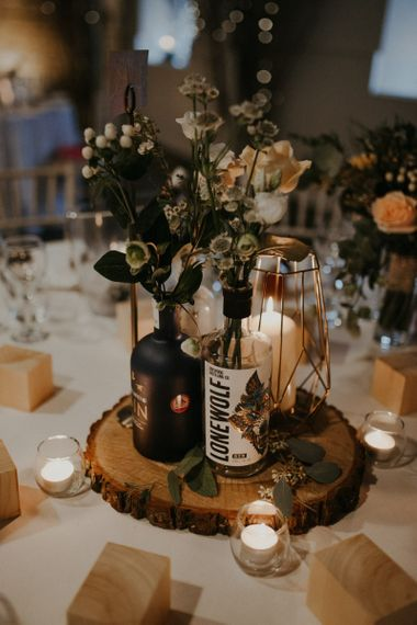 Rustic centrepiece decor with tree slice, fairy lights, gin bottles and flower stems