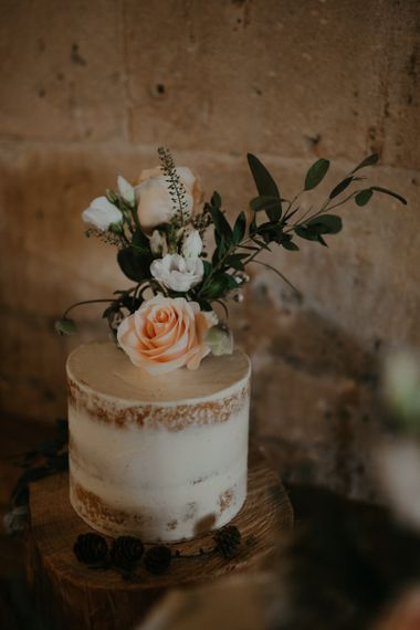 Small semi naked wedding cake with flower topper