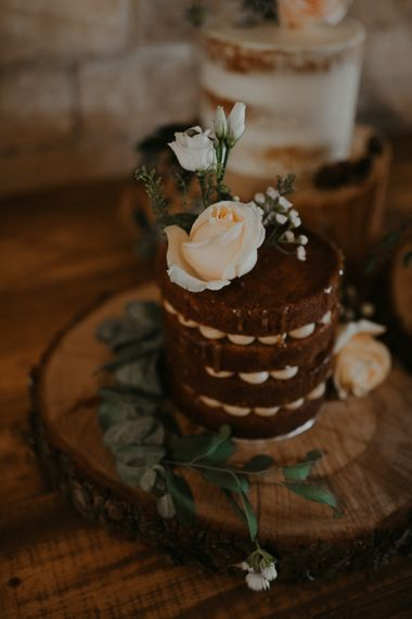 Individual chocolate wedding cake on tree slice with flower decor
