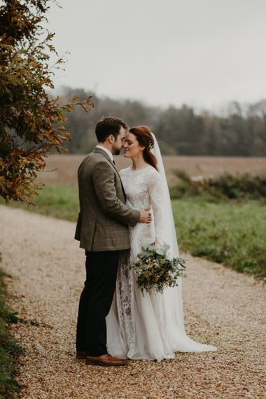 Groom in wool blazer embracing his bride in Grace Loves Lace wedding dress
