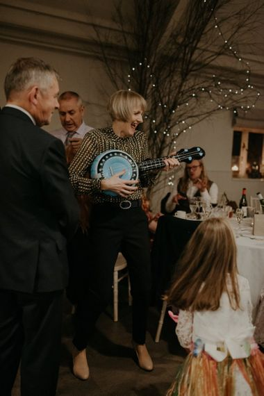 Wedding guest playing with inflatable guitar