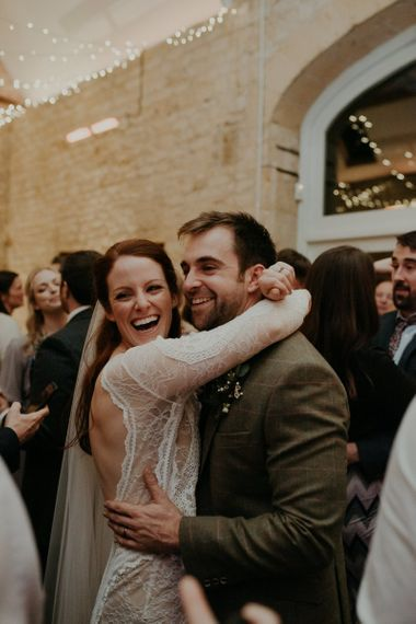 Bride and groom embracing and laughing on the dance floor at Lapstone Barn