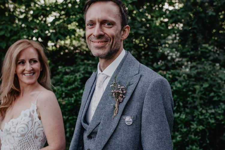 Groom in grey three piece suit with floral buttonhole