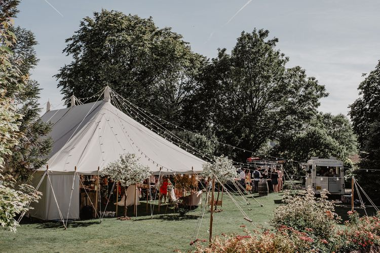 Marquee reception with stunning cherry blossom trees and Prosecco wall
