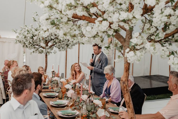 Cherry blossom trees at wedding with Prosecco wall