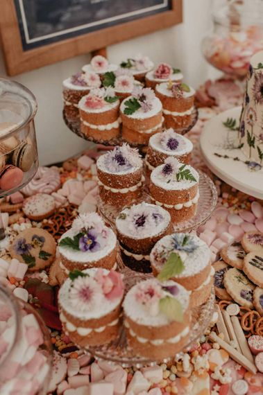 Wedding cupcakes on cake table at wedding with Prosecco wall