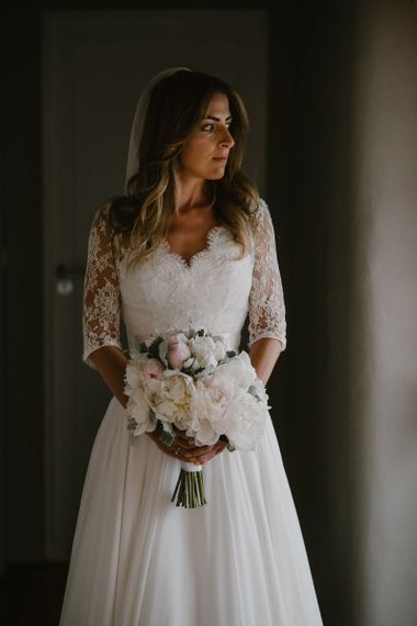 Beautiful Bride in Naomi Neon Wedding Dress with Lace Bodice and Three Quarter Sleeves Holding Her Peony Wedding Bouquet