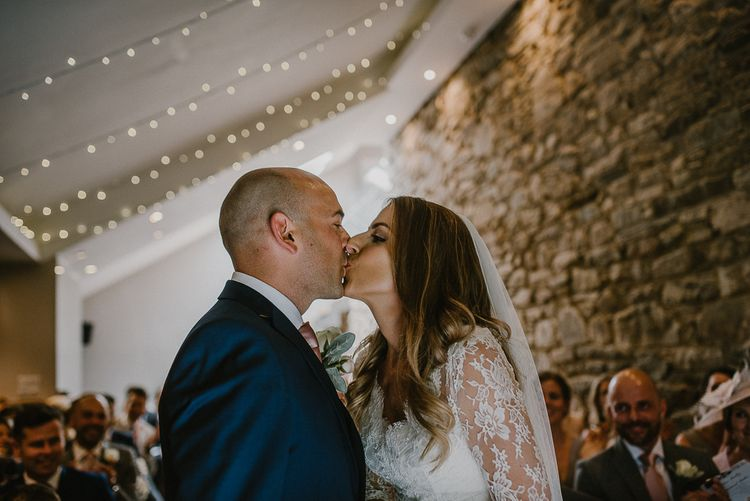 Bride and Groom Kissing During The Wedding Ceremony with Fairy Light Decorated Ceiling